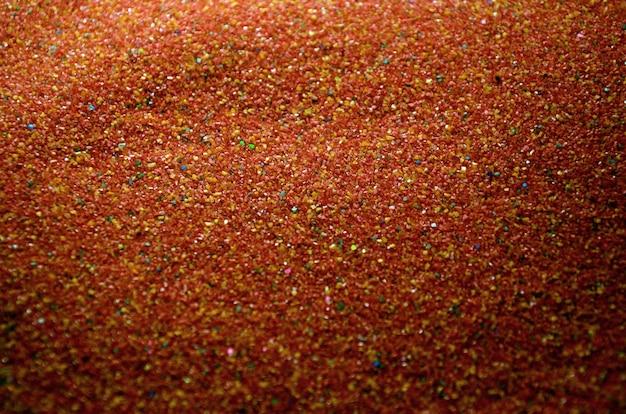 Beschaffenheit eines farbigen körnigen sandabschlusses oben. rote körner