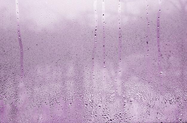 Beschaffenheit eines tropfens des regens auf einem nassen transparenten glashintergrund. in rosa farbe getönt