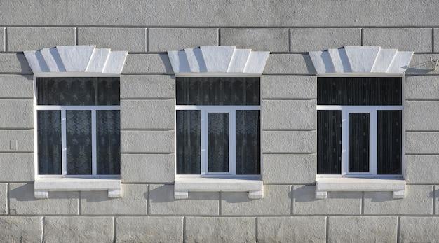 Beschaffenheit von glasig-glänzenden modernen fenstern eines grauen konkreten gebäudes