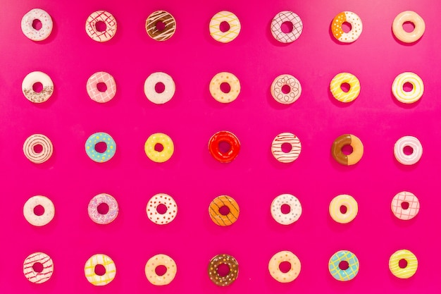 Beschaffenheit von mehrfarbigen schaumgummiringen auf rosa hintergrund. süßigkeiten und essen