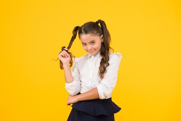 Bescheidene frisur. nettes kleines schulkind, das frisur um ihren finger auf gelbem hintergrund wickelt. modemädchen mit langer pferdeschwanzfrisur im formalen stil. styling-frisur für kleine kinder für die schule.