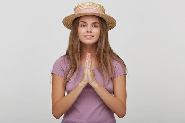 Bescheidene junge frau im strohhut, betet für wellness