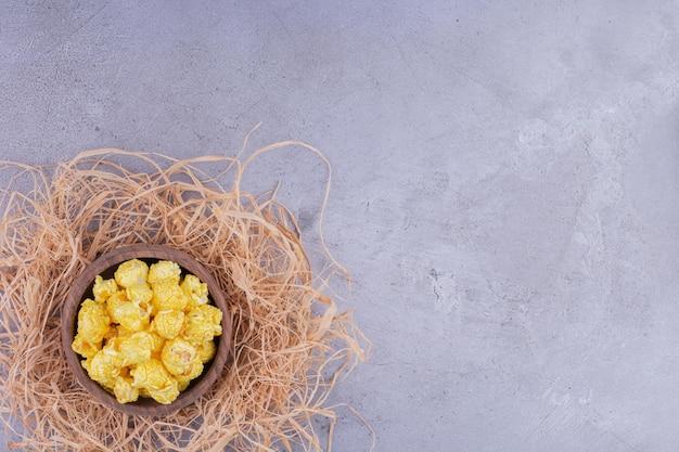 Bescheidene schüssel auf einem strohhaufen gefüllt mit mit süßigkeiten überzogenem popcorn auf marmorhintergrund. foto in hoher qualität