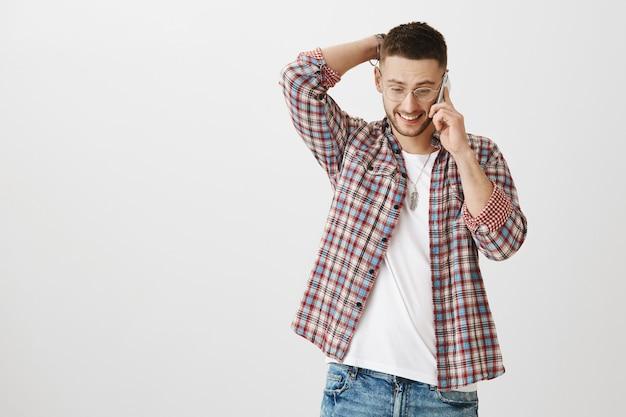 Bescheidener hübscher junger mann, der mit seinem telefon aufwirft