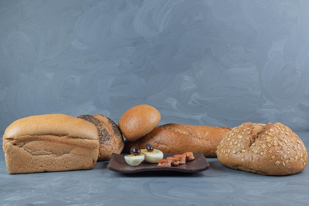 Bescheidenes frühstück, umgeben von brotlaiben auf marmortisch.