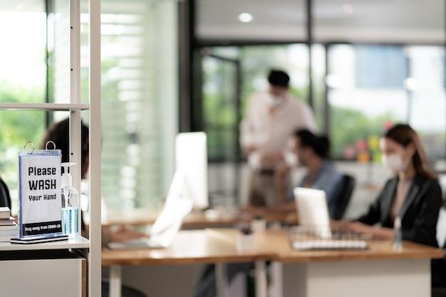 Beschilderung des händedesinfektionsmittels im büro für die hygienepraxis nach der wiedereröffnung. geschäftsleute arbeiten und tragen eine gesichtsmaske in einem neuen normalen büro, um die ausbreitung des covid-19-virus zu verhindern