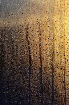 Beschlagenes glas mit vielen tropfen und tropfen kondensation gegen das sonnenlicht im morgengrauen