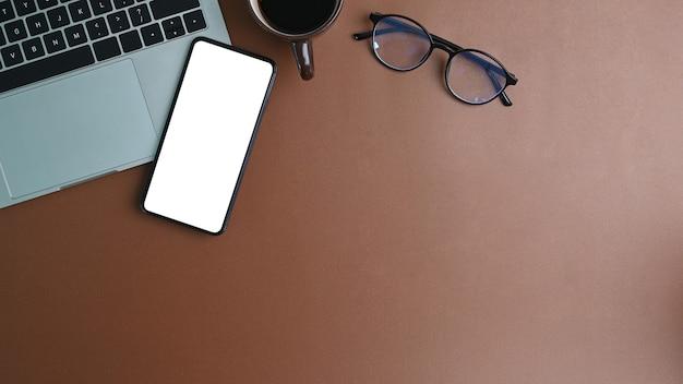 Beschneidungspfadbildschirm des smartphones auf braunem lederarbeitsplatz mit draufsichtschuß.