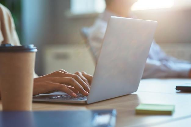 Beschnitten von einem büroangestellten, der einen laptop benutzt, während er im modernen büro am schreibtisch sitzt