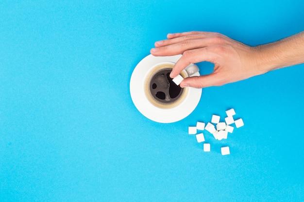 Beschnittene ansicht der frau, die klumpenzucker zum kaffee auf blau lokalisiert hinzufügt