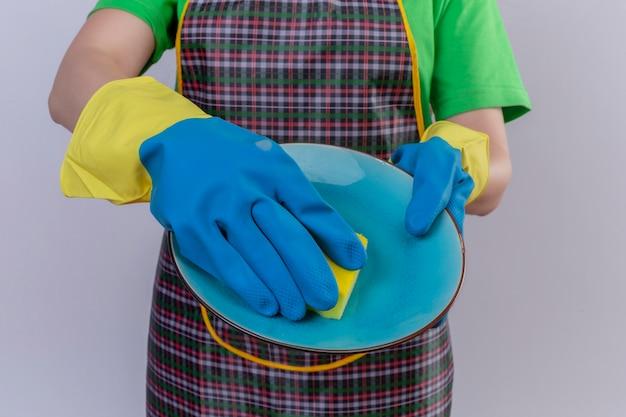 Beschnittene ansicht der frau, die schürze und gummihandschuhe trägt, die geschirr in handwaschplatte halten