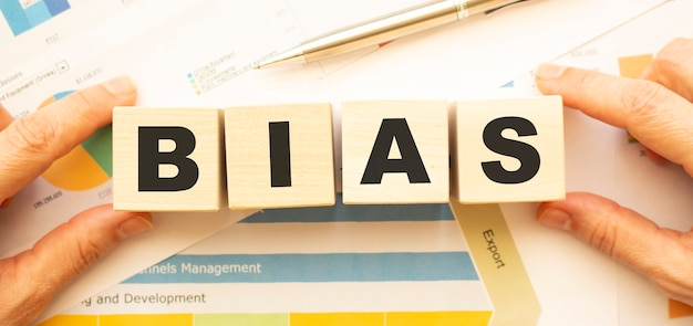 Beschnittene ansicht der hände, die holzwürfel mit bias-beschriftung auf arbeitstisch halten.