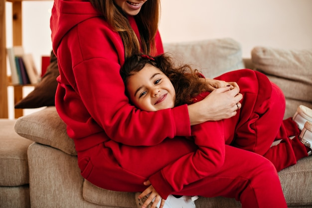 Beschnittene ansicht der lachenden mutter, die tochter zu hause umarmt. innenaufnahme des lachenden kindes, das spaß mit mutter hat.