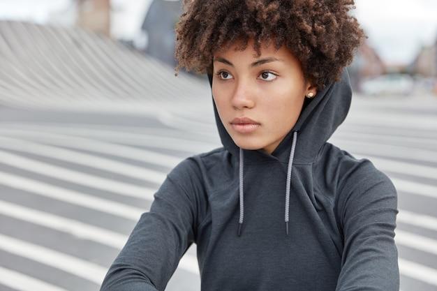 Beschnittene ansicht der nachdenklichen dunkelhäutigen jungen sportlerin im stilvollen kapuzenpulli