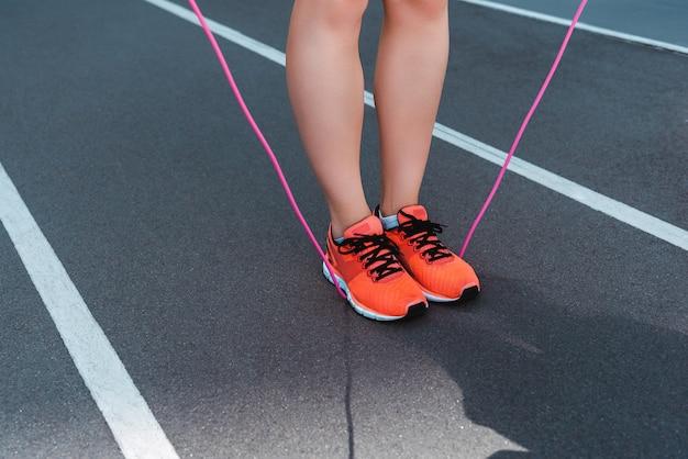 Beschnittene ansicht der sportlerin in turnschuhen, die springseil auf laufbahn halten