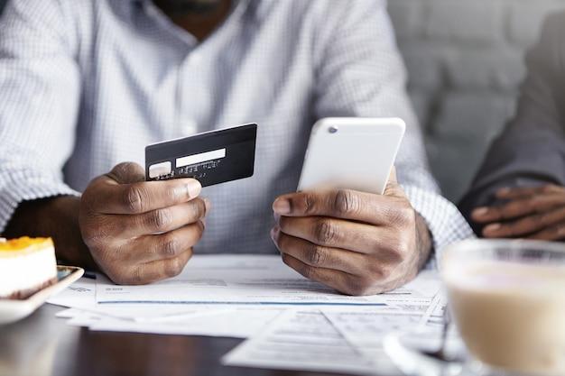 Beschnittene ansicht des afroamerikanischen businesman, der handy und kreditkarte hält, während rechnung im café zahlt