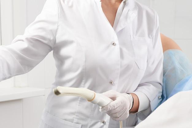 Beschnittene ansicht des gynäkologen, der transvaginalen ultraschallstab hält, um eine frau zu untersuchen