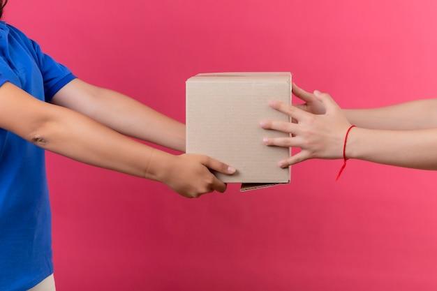 Beschnittene ansicht des liefermädchens, das einem kunden boxpaket über isoliertem rosa raum gibt