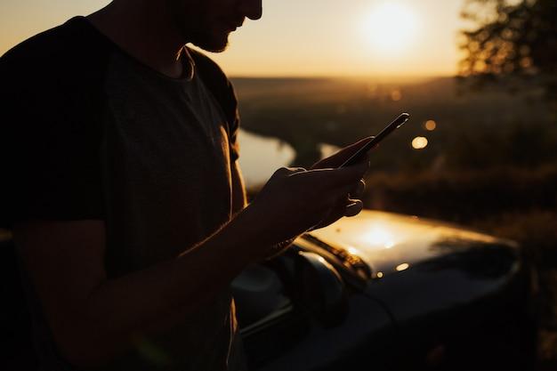 Beschnittene ansicht des männlichen hipsters, der smartphone auf natur bei sonnenuntergang hält.