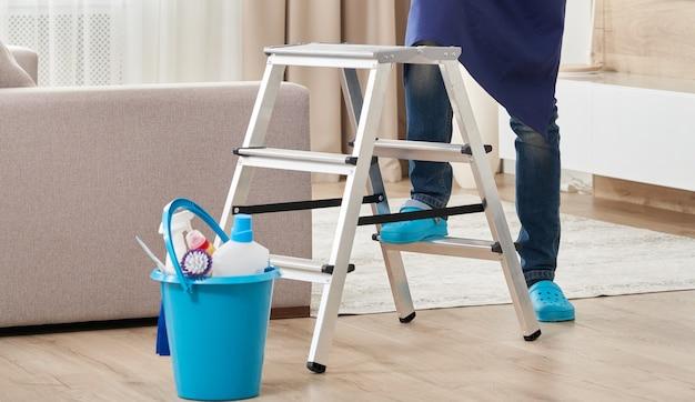 Beschnittene ansicht des mannes, der leiter klettert, um decke zu reinigen. reinigungsservicekonzept
