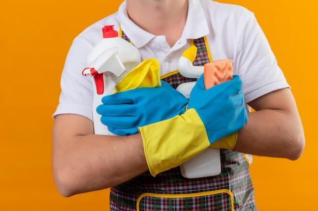 Beschnittene ansicht des mannes, der schürze und gummihandschuhe trägt, die reinigungsmittel und schwamm über lokalisiertem orangefarbenem hintergrund halten