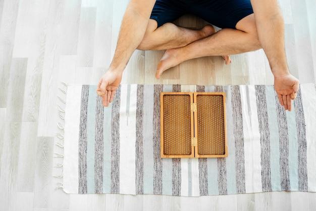 Beschnittene ansicht des mannes, der yoga meditiert und auf dem boden nahe sadhu brett sitzt