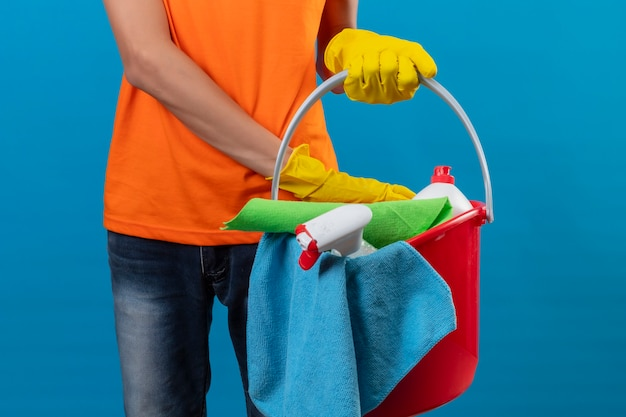Beschnittene ansicht des mannes im orangefarbenen t-shirt, das gummihandschuhe trägt, die roten eimer voll von reinigungswerkzeugen über isoliertem blauem raum halten