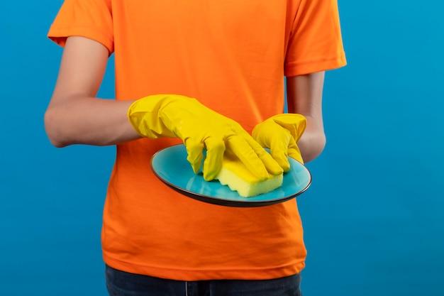 Beschnittene ansicht des mannes im orangefarbenen t-shirt und in den gummihandschuhen, die einen teller über isoliertem blauem raum waschen