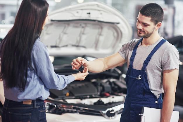 Beschnittene ansicht des mechanikers, der dem weiblichen kunden autoschlüssel gibt