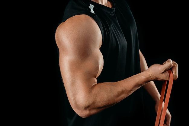 Beschnittene ansicht des muskulösen bodybuilders, der mit dem auf schwarz isolierten widerstandsband trainiert