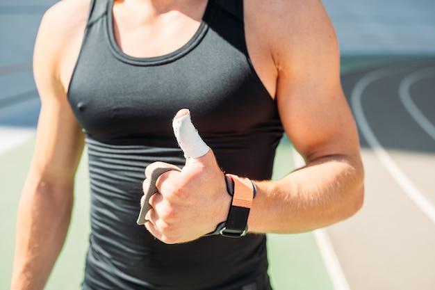Beschnittene ansicht des sexy bodybuilders, der daumen hoch zeigt