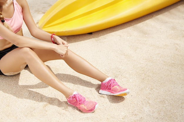 Beschnittene ansicht des weiblichen läufers, der rosa laufschuhe trägt, die auf sand nach aktiver körperlicher übung im freien ruhen. junge sportlerin in sportbekleidung, die am strand während des morgentrainings entspannt
