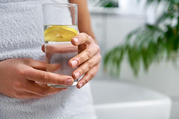 Beschnittene ansicht einer frau, die ein glas wasser und zitrone am badezimmer hält