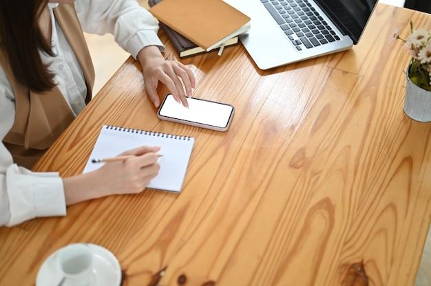 Beschnittene aufnahme der desingner-frau, die ihr projekt auf notizbuch schreibt, während smartphone mit weißem bildschirm verwendet wird