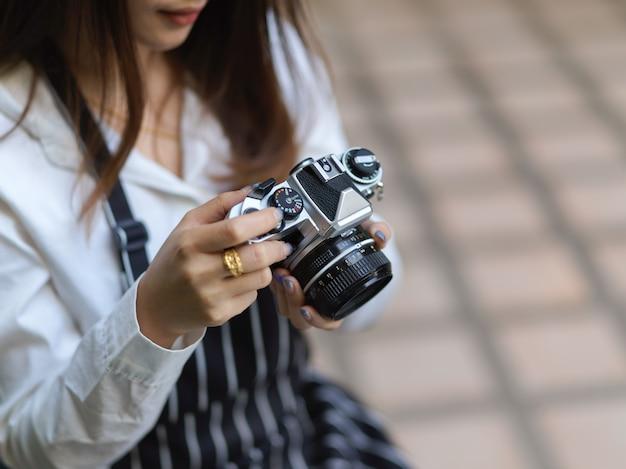 Beschnittene aufnahme der fotografin mit schürze, die bild auf digitalkamera überprüft, während foto im café nimmt