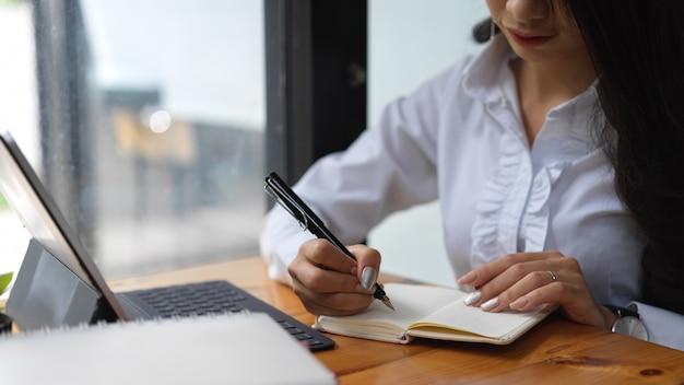 Beschnittene aufnahme der frau, die mit digitalem tablett arbeitet und eine idee in ihr notizbuch schreibt