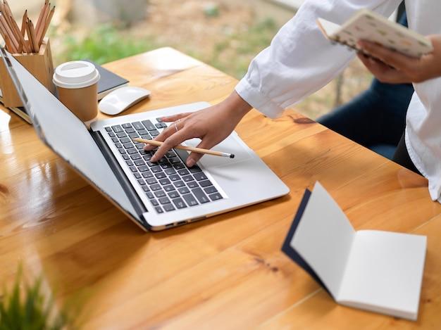 Beschnittene aufnahme der geschäftsfrau, die an ihrem projekt arbeitet, während notebook hält und auf laptop-computer tippt