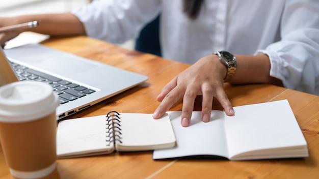 Beschnittene aufnahme der geschäftsfrau, die an ihrem projekt arbeitet, während notebook im arbeitsbereich verwendet wird