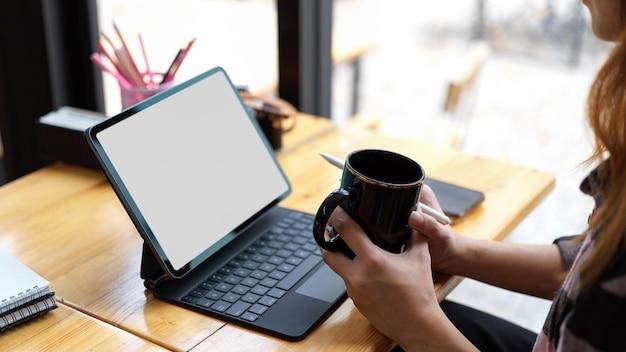 Beschnittene aufnahme der jungen frau, die kaffeetasse hält, während sie an ihrem projekt mit tablett des leeren bildschirms arbeitet