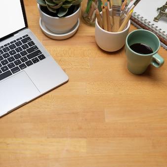 Beschnittene aufnahme des arbeitsbereichs mit laptop, kaffeetasse, zubehör und kopierraum im arbeitszimmer zu hause
