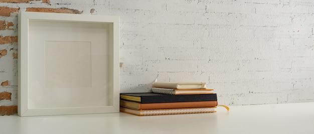 Beschnittene aufnahme des arbeitstisches mit modellrahmen, büchern, notizbüchern und kopierraum im home-office-schreibtisch