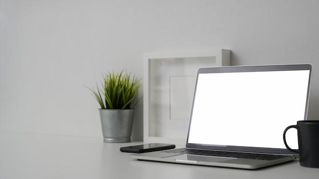 Beschnittene aufnahme des bequemen arbeitsbereichs mit laptop mit leerem bildschirm und dekorationen auf weißem tisch