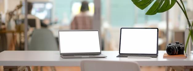Beschnittene aufnahme des bequemen schreibtischs mit laptop, tablet, kamera, büromaterial und dekoration