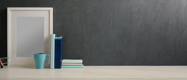 Beschnittene aufnahme des home-office-schreibtisches mit modellrahmen, büchern, becher und kopierraum