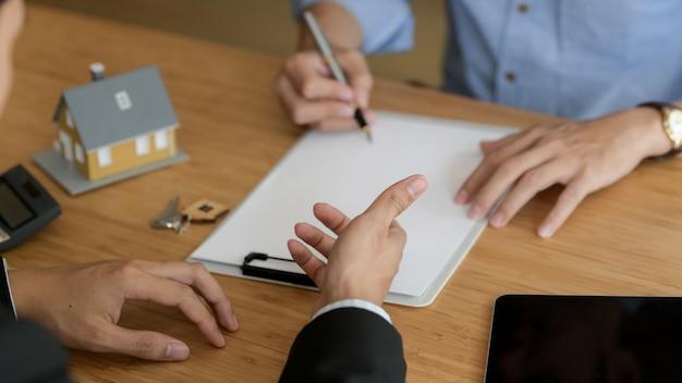 Beschnittene aufnahme des immobilienmaklers, der dem männlichen kunden präsentiert