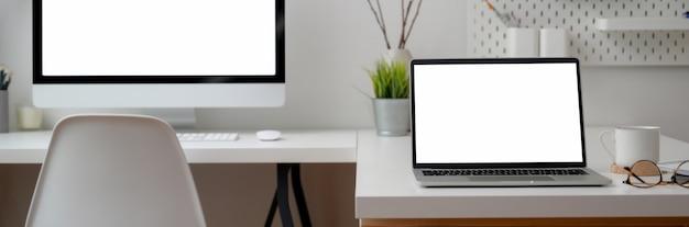 Beschnittene aufnahme des schreibtischs mit computergeräten, zubehör und dekorationen auf weißem tisch