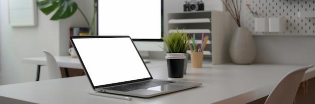 Beschnittene aufnahme des schreibtischs mit computergeräten, zubehör und dekorationen