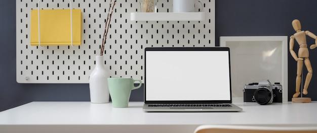 Beschnittene aufnahme des stilvollen arbeitsbereichs mit modell-laptop, dekorationen und büromaterial