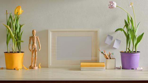 Beschnittene aufnahme des stilvollen arbeitsbereichs mit rahmen, blumentöpfen und schreibwaren im wohnzimmer