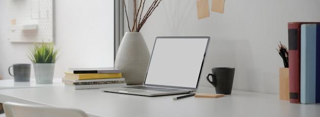Beschnittene aufnahme des tragbaren arbeitsbereichs mit laptop, becher, büchern, notizblock und dekoration